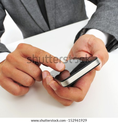 a businessman sitting in a table using a smartphone - stock photo