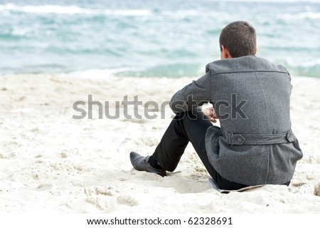 A businessman sitting on the beach alone enjoying the view - stock photo