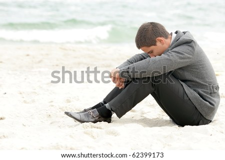 A businessman sitting on the beach depressed - stock photo