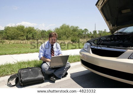 A businessman sitting on the curb working beside his broken down car. - stock photo