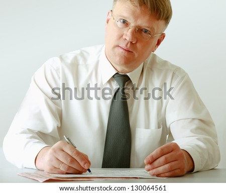 A businessman sitting on the desk and writing, isolated on white background