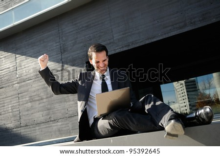 A businessman sitting on the floor with a laptop computer, rising his arm - stock photo