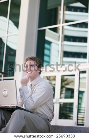 A businessman sitting on the stairs of a business building with his laptop on his legs and his hand on his chin with a smile on his face