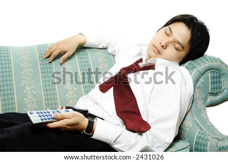 A businessman sleeping on a couch holding a TV remote - stock photo