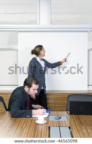 A businessman slowly falling asleep during a presentation - stock photo
