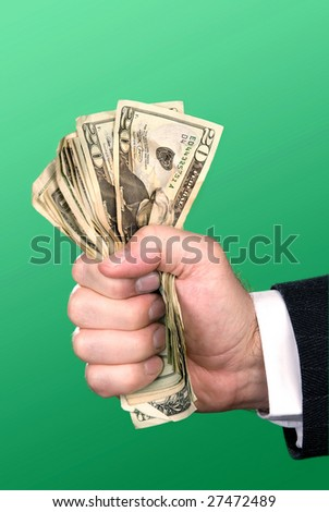 A businessman squeezes a fist full of cash. - stock photo