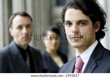 A businessman standing in front of two colleagues (shallow depth of field used)