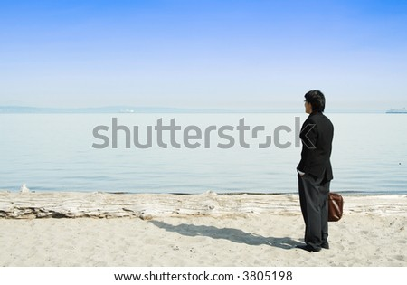 A businessman standing on the beach alone enjoying the view
