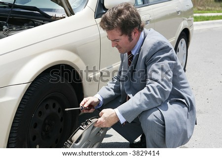 A businessman, stranded with a flat tire, removes his hubcap. - stock photo