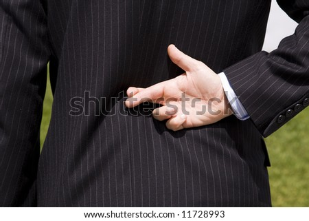 a businessman telling a lie with the fingers crossed - stock photo