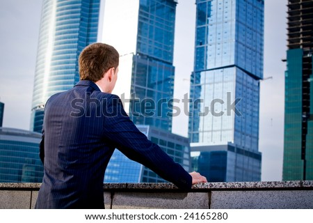 A businessman thinks about the future of business outdoors - stock photo