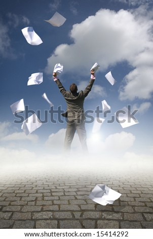 A businessman throwing paperwork in the air. - stock photo