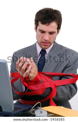 A businessman tied up in red tape - stock photo