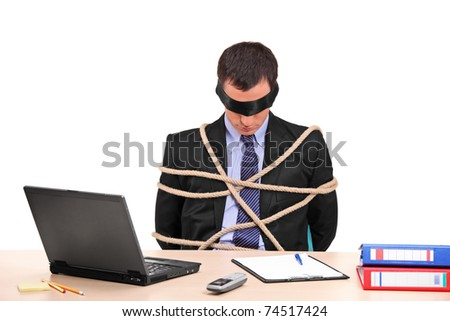 A businessman tied up with rope in his office isolated against white background - stock photo