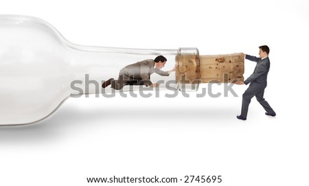 A businessman trapped inside a bottle trying to crawl out through the neck with his partner pulling on the cork from the outside - stock photo