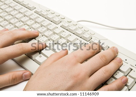 A businessman typing on a white keyboard