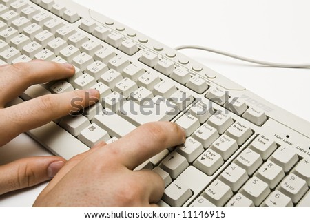 A businessman typing on a white keyboard - stock photo