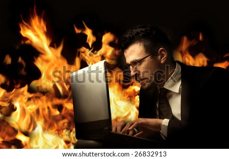 a businessman using a laptop with flames on the background