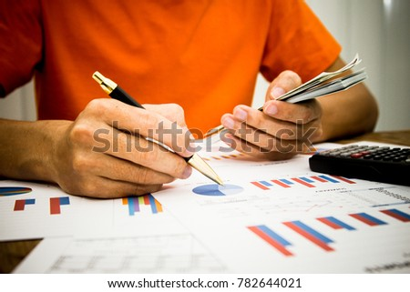 A businessman using calculator and holding money for calculate tax in office.