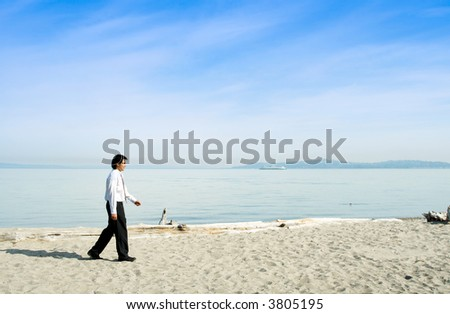 A businessman walking along the beach alone