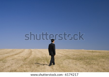 a businessman walking in the field - stock photo