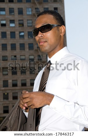 A businessman walks through downtown during a sunny day.