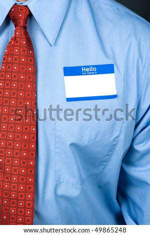 A businessman wearing a blank nametag and bright red tie with a blue shirt. - stock photo