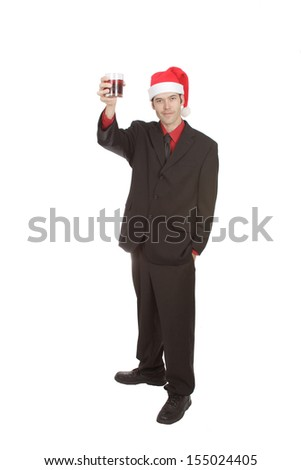 A businessman wearing a dark suit, red top and Santa hat. He holds a glass in his hand and looks ready to make a toast. Isolated on white. - stock photo