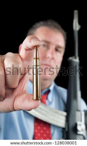 A businessman wearing a dress shirt and necktie shows off a large 223 bullet for his assault rifle. - stock photo