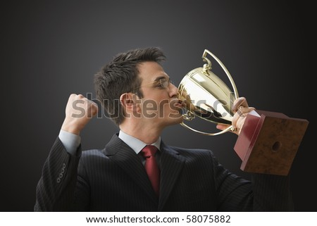 A businessman wearing glasses is holding a trophy and kissing it. Horizontal shot.