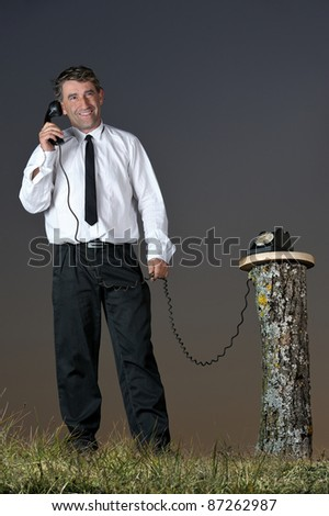 a businessman who phone in the countryside - stock photo