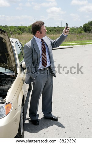 A businessman whose care has broken down in a remote location checking for phone signal. - stock photo