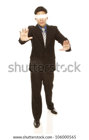 A businessman with a blindfold walking with no direction (isolated on white) - stock photo