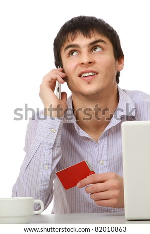 A businessman with a credit card, laptop at the desk looking up, over white - stock photo