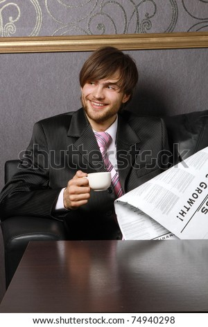 A businessman with a cup of coffee and a newspaper - stock photo