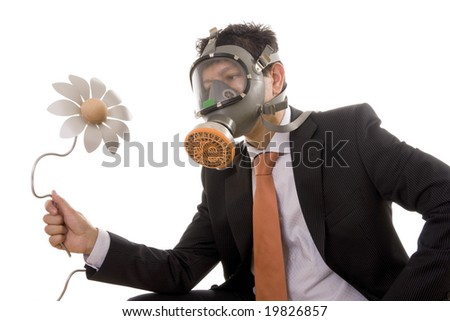 A businessman with a gas mask looking to an artificial flower