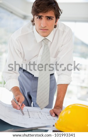 A businessman with a hard hat and construction drawings - stock photo