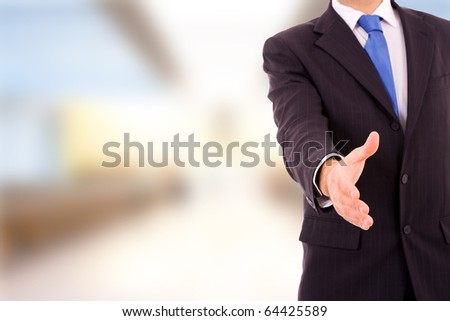 A businessman with an open hand ready to seal a deal at the office - stock photo