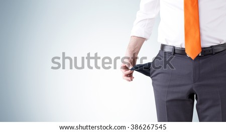 A businessman with an orange tie turning his empty pockets inside out. Front view, no head. Grey background. Concept of bankruptcy. - stock photo
