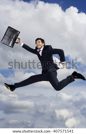 A businessman with briefcase, leaping in the air - stock photo