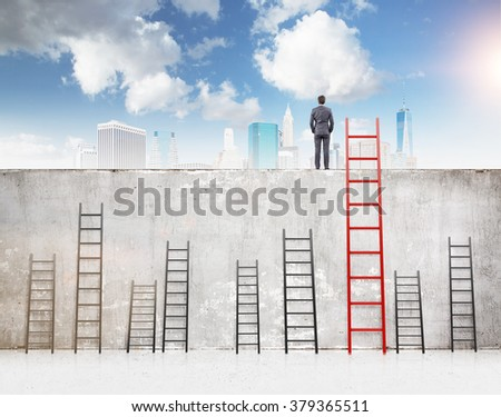 A businessman with hands in pockets standing on a concrete wall separating him from New York. Several ladders of different size at the wall, blue sky above. Concept of reaching aim. - stock photo