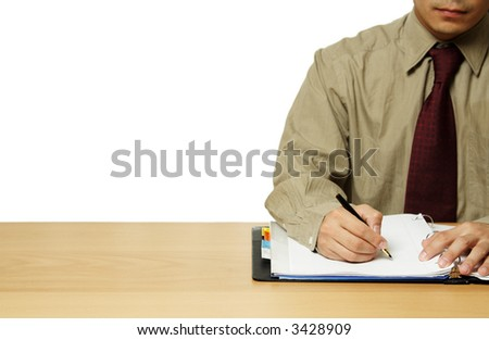 A businessman working and writing at his office