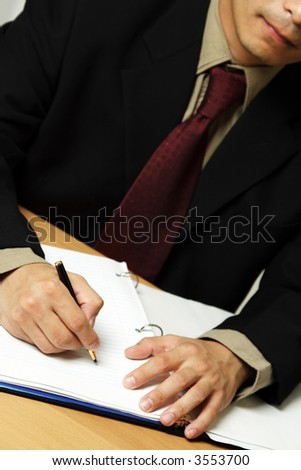 A businessman working and writing at his office - stock photo