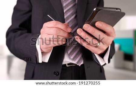 A businessman writing a message with a stylus on an electronic device.