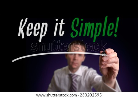 A businessman writing Keep It Simple on a screen. Business Concept.