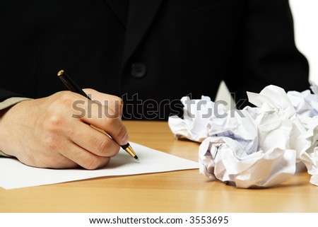 A businessman writing on a piece of paper