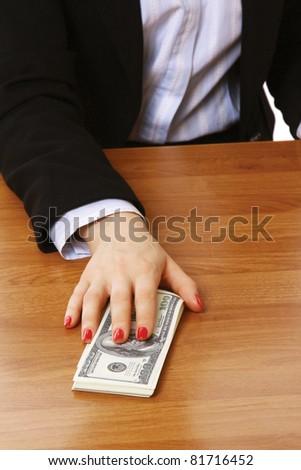 A businessperson holding dollar bills on a desk - stock photo