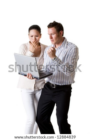 A businesswoman and businessman expressing excitement looking at a laptop they are holding