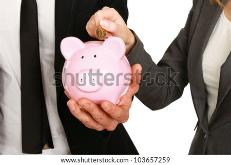 A businesswoman and man putting a coin into a piggy bank isolated on white background