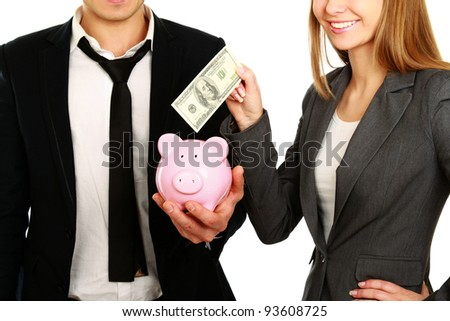 A businesswoman and man putting a money into a piggy bank isolated on white background